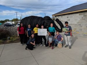 students standing with elephant sculpture made from recycled tires